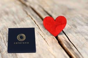 Valentinstag - Collage aus rotem Herz und blauem colorano Schmuck Etui auf hellem Holz