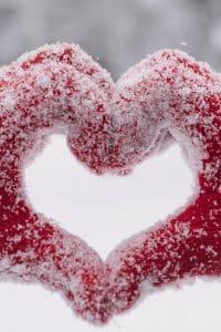 Aus zwei Händen mit schneebedeckten, roten Handschuhen geformtes Herz
