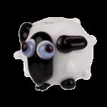 drollig blickendes Schaf aus glas mit blauen Augen schwarzer langer nase und schwarzen öhrchen auf weissem koerper gefertigt von colorano