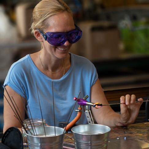 teilnehmerin des glasperlen workshops im makerspace rhein-neckar fertigt am brenner eine glasfigur an und hat zum schutz eine spezielle schutzbrille auf