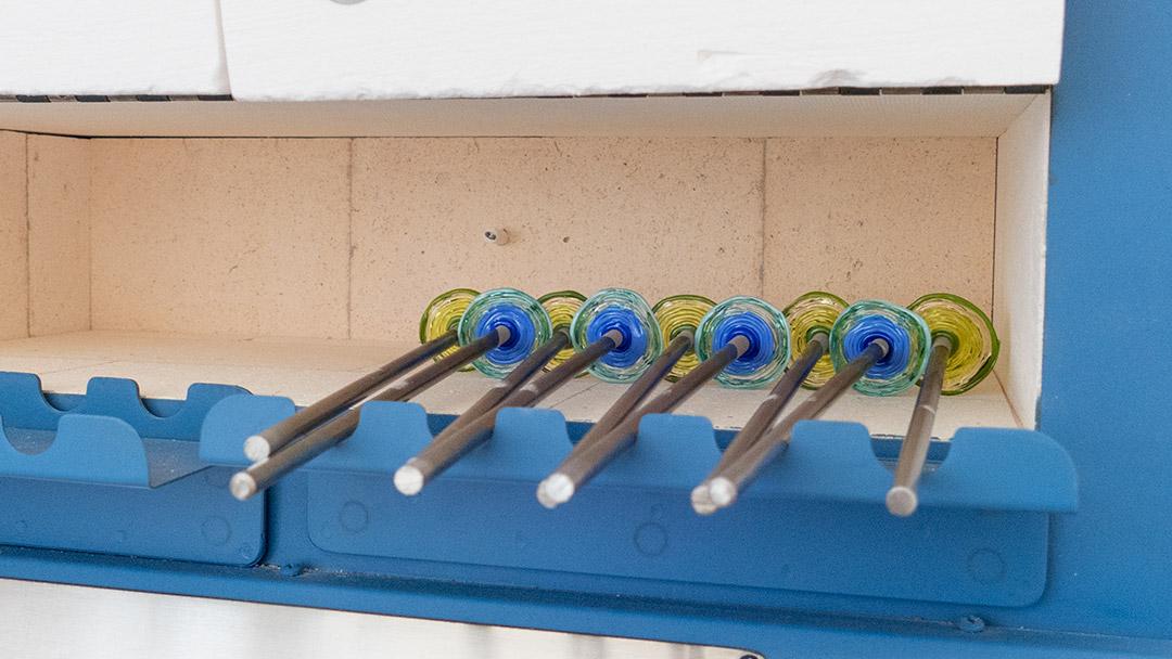 Glasschmuck aus blau-tuerkisem und gruenem Glas im Temperofen nach der Abkühlung
