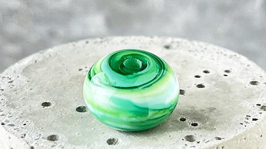 grün-weiße Glasperle auf einem Podest aus Beton